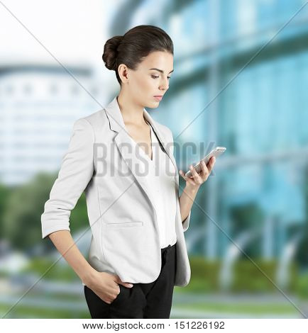 Businesswoman with phone on blurred building background. Lawyer and notary concept.
