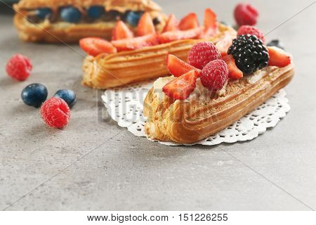 Delicious eclairs with berries and doily on light textured background