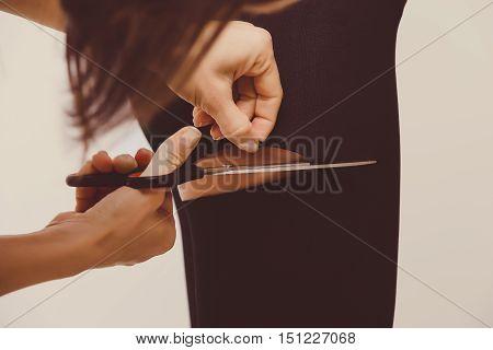 female hands scissor, cutting tights on beautiful woman legs in black nylon pantyhose