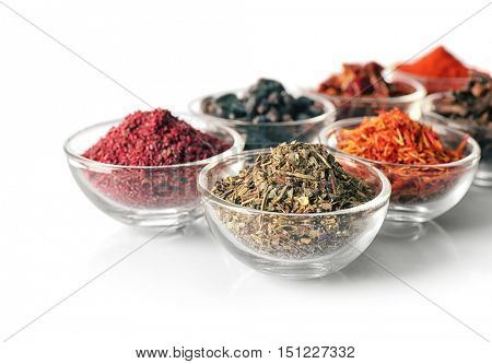 Assortment of spices in glass bowls on white background