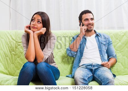 Young couple is sitting on sofa at home. Woman is getting bored while man is typing on phone.