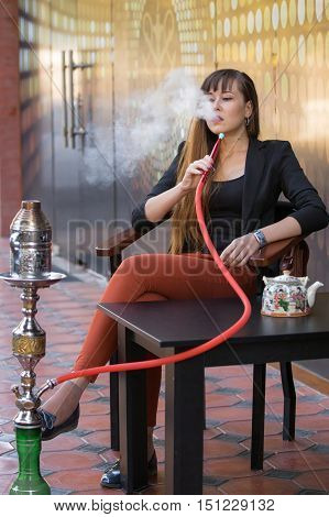 young smart casual woman smoking hookah and drinks Chinese tea in cafe focus on woman