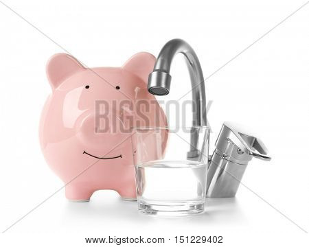 Metal tap and pig money box isolated on white. Water saving concept