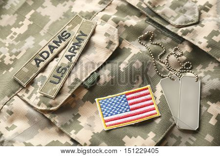 Soldier's tokens and little American flag on camouflage fabric background