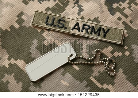Soldier's token on camouflage fabric background