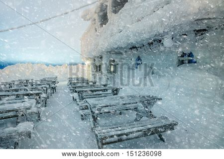 Dangerous winter weather at night - snow, blizzard, cold and nobody. Old wooden house covered snow, winter scene