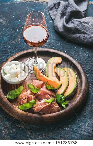 Italian antipasti snack for wine. Prosciutto ham, cantaloupe melon, mozzarella cheese, fresh basil leaves and glass of rose on wooden round serving board over grunge dark plywood background, selective focus