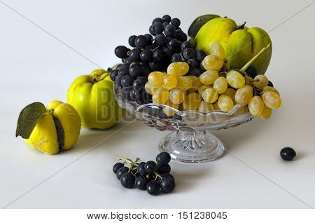 Assorted autumn fruits - grapes, quince - in a small crystal vase on a white background isolated