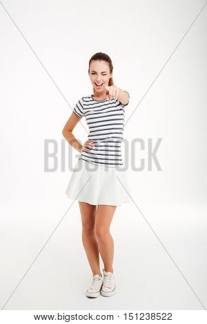 Full length portrait of a happy playful woman pointing finger at camera and winking isolated on a white background