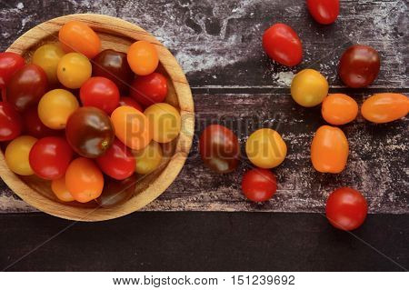 Fresh ripe colorful grape tomatoes on wooden background