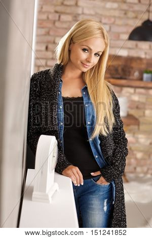 Beautiful blonde woman smiling at home, leaning against wall in casual clothes.