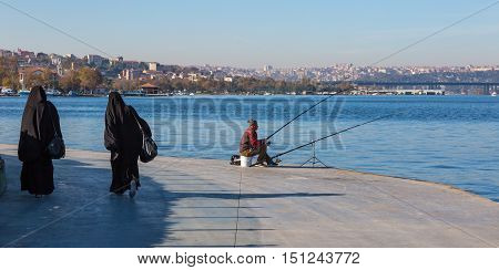 Fisherman sitting at Seafront Promenade and two Muslim dressed Ladies walking urban Middle Eastern City scape on Background. Istanbul, Turkey, November 20, 2015