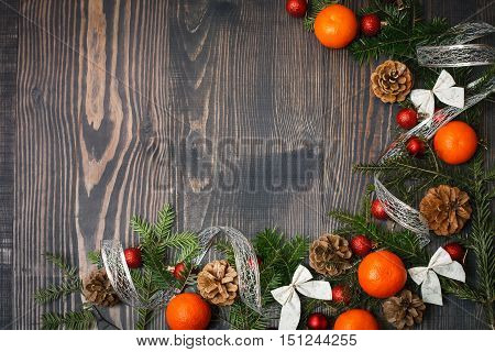 Red Christmas balls fir branches and tangerines on a wooden background