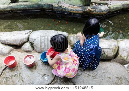 Asian Chinese Little Girls Fishing With Scoop Net At Pond