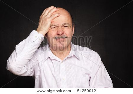 Older Man In White Shirt Hugged His Head, Wincing.