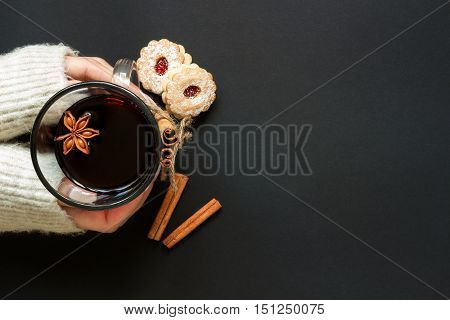 Hands Holding Wineglass Of Hot Wine With Cookies Top View