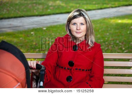 Blond Woman In Red Coat Holding Handle Or Pram.