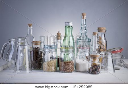 Still life of transparent glass bottles, cans and glasses on a white wooden table.