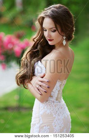 Beautiful brunette Bride Wedding Portrait woman with long wavy hair wearing in white lace wedding dress posing in green park.