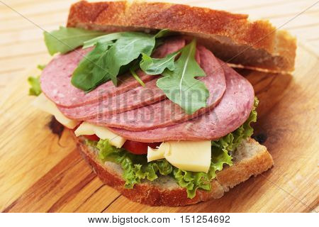 Baloney or Bologna sausage sandwich with cheese, lettuce and rocket salad