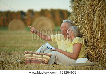 Beautiful happy senior couple in summer field with magazine