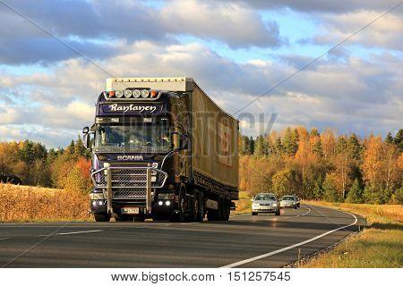 SALO FINLAND - OCTOBER 7 2016: Purple Scania R500 semi truck of JR-Trans hauls cargo trailer along scenic road on autumn evening.