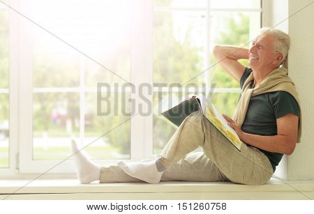Senior man with book sitting on the windowsill at home