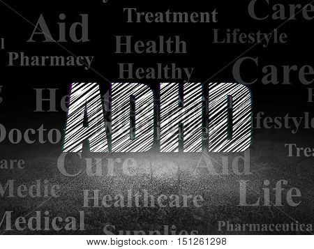 Health concept: Glowing text ADHD in grunge dark room with Dirty Floor, black background with  Tag Cloud