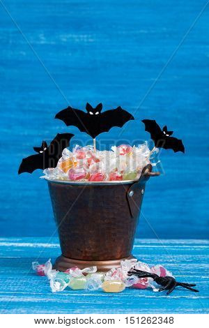Halloween candy bucket paper bats and rubber spider on blue wooden backround vertical orientation