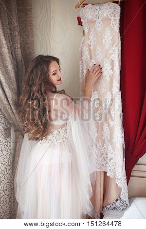 Wedding Preparation. Beautiful Brunette Bride Smiling In Sexy Underwear Touching Lace Bridal Dress.