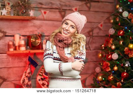 Lovely Happy Woman. Merry Christmas. Young female wearing warm clothes, cosy sweater, hat and scarf, smiling over christmas tree decorations.