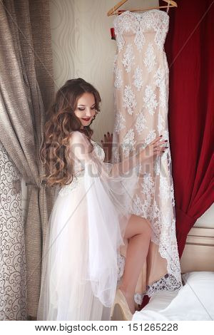 Wedding Preparation. Beautiful Brunette Bride Smiling In Sexy Underwear Admire The Lace Bridal Dress