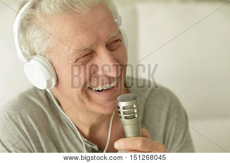 Senior man  singing into microphone in headphones