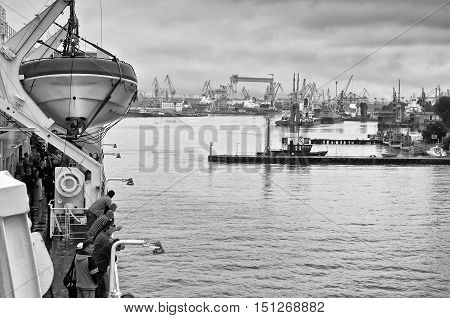 Gdynia Poland - August 7 2010: Passengers arriving at the Gdynia port by ferry. View of the shipyard on the background of Gdynia Poland at August 7 2010. Black and white photography.