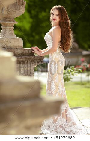 Bride. Wedding Outdoor Portrait Of Gorgeous Brunette Model With Long Wavy Hair Wearing In White Fash