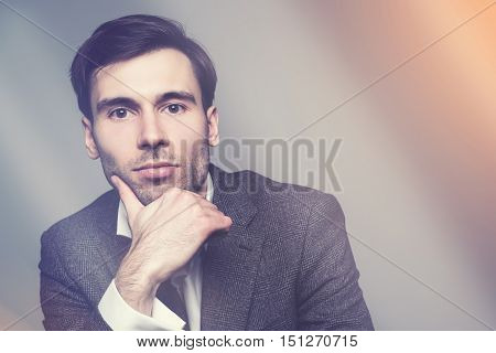 Businessman with hand at chin against dark background. Toned image