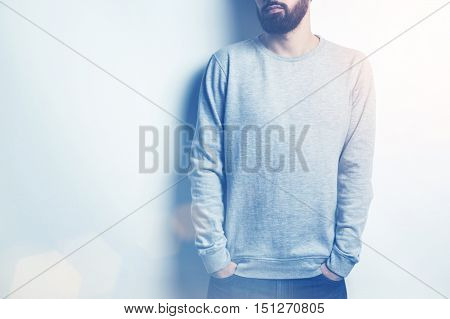 Young man in long sleeved sweatshirt on light grey background. Toned image. Mock up