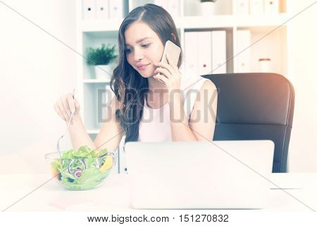 Woman in office eating salad at working place. Laptop at table. She is on her phone. Bookshelves with binders plants and coffee at background. Sunny. Concept of lunch at work. Toned image
