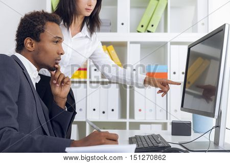 African American guy is looking at large computer monitor. His personal assistant is showing him data. Concept of boss secretary relationship