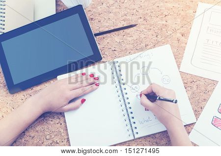 Woman With Red Nails Drawing In Her Notebook