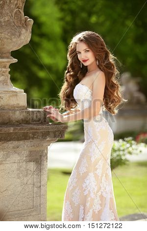 Wedding Portrait Of Gorgeous Bride With Long Wavy Hair Wearing In White Lace Wedding Dress Holding P