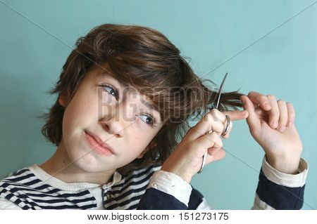 preteen handsome boy with scissors try to cut his hair by himself close up photo