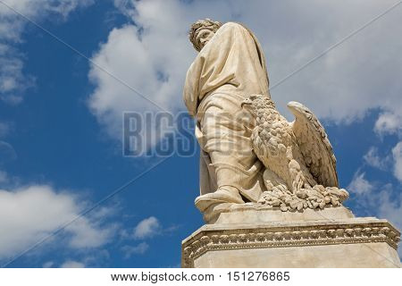 Low angle view of eagle and statue of Durante degli Alighieri, also called Dante in the Piazza di Santa Croce in Florence, Italy. Dante is Italian poet of the late Middle Ages