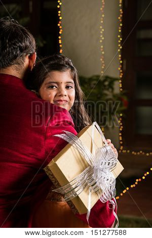 Indian young Father giving gift to his daughter on diwali, diwali gift, indian girl child hugging father on diwali night with gift in hand, happiness concept