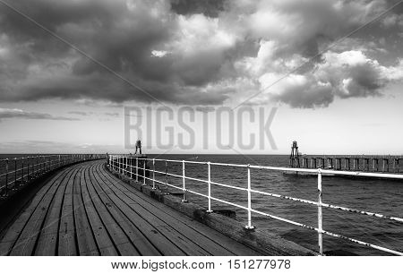 Black and white image of Whitby pier at the harbour entrance at Whitby in North Yorkshire UK