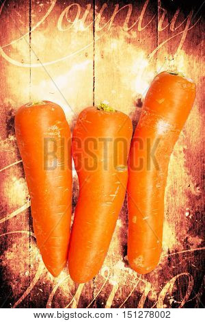 Close-up of fresh delicious carrots on obsolete wooden background with text. Country cooking poster