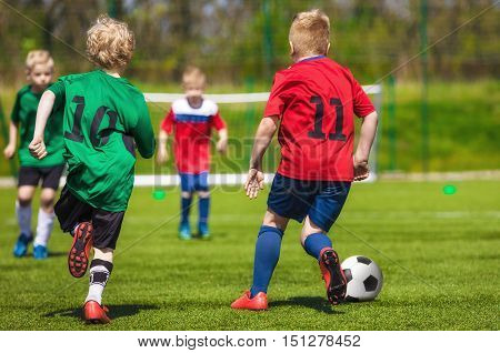 Young football soccer players running and kicking ball on sports field. Youth sport soccer league. Football match for children