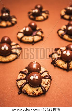 Halloween decorated creepy and delightful peanut butter spider cookies with chocolate truffle on brown surface