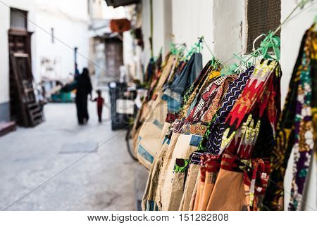 variety of colorful bags hung on african street for sale