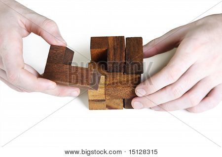 Closeup Of Mans Hands Assembling Wooden Cube Puzzle, Isolated